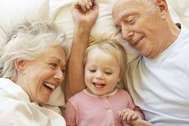 image of grandparent child  - Grandparents Cuddling Granddaughter In Bed - JPG