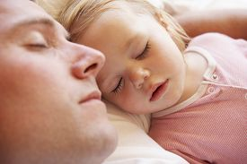 stock photo of pyjama  - Father And Daughter Sleeping In Bed - JPG