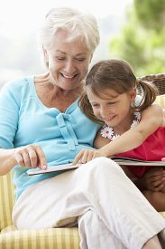 foto of grandmother  - Grandmother And Granddaughter Reading Book On Garden Seat - JPG