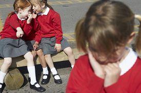 stock photo of playground school  - Female Elementary School Pupils Whispering In Playground - JPG