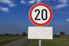 pic of mile  - Twenty miles per hour speed limit sign against a partly cloudy sky - JPG
