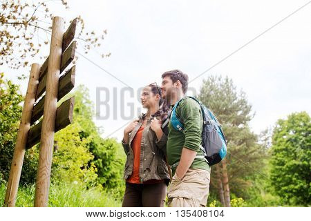 adventure, travel, tourism, hike and people concept - smiling couple with backpacks standing at sign