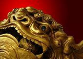 Golden Chinese lion statue with red background
