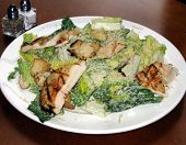 image of caesar salad  - this is an image of a chicken caesar salad on a wooden table - JPG