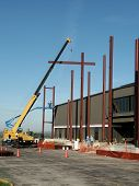 pic of commercial building  - workers placing steel beams in front of building - JPG