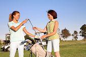Two pretty women golfers selecting a golf club