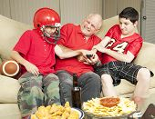 American football fans- father and sons - fighting for the television remote control.