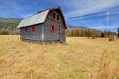 Cute Grey And Red Rustic Old Barn In The Fieild