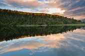 Sunrise Above A Lake On A Wind Still Morning