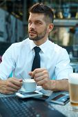Portrait of confident businessman drinking espresso and using laptop at sidewalk cafe. poster