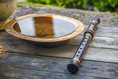 Indian Flute On A Table With Ancient  Brass Plate With Water. Close Up. poster