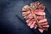 Barbecue dry aged wagyu porterhouse steak sliced as top view on a burnt board with copy space left  poster