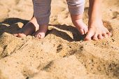 Parent And Child Walking Barefoot. Mother And Cute Little Baby Feet On Summer Beach Sand. Family On  poster