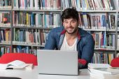 Happy Male Student With Laptop In Library poster