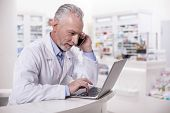 Important Call. Senior Handsome Male Pharmacist Male Pharmacist Working On Laptop While Making Call poster