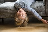 Cute Funny Boy Lying Upside Down On Sofa Looking At Camera, Smiling Playful Preschool Child Having F poster