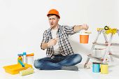 Shocked Man In Orange Protective Helmet Sitting On Floor With Paint Can, Instruments For Renovation poster