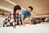 Tidy Bearded Father With Young Son Is Testing Mattress For Softness. Testing Softness Of Mattress. C poster
