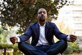 Young American African Businessman In Informal Clothes Meditating In Lotus Pose Taking A Deep Breath poster