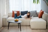 Side View Of Young Female Lying On Couch And Using Digital Tablet In Living Room With Modern Interio poster