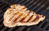 stock photo of t-bone steak  - T bone steak on the hot grill - JPG