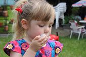 Cheeky young girl blowing bubbles