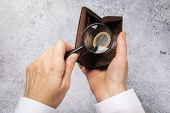 One Euro In The Wallet. A Man Is Looking For Money In A Wallet With A Magnifying Glass. Small Income poster