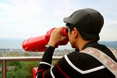 Young Man Observing Aerial City View With Binoculars From The Observation Deck poster