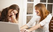 Two Young Women Having Fun In Front Of Laptop
