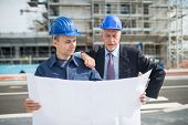 Architect explaining what work to do to the site manager in front of a construction site building poster