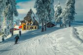 Winter Ski Resort With Wooden Lodges Near Ski Piste. Snow Covered Pine Trees And Sporty Skiers On Th poster
