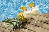 picture of pina-colada  - Two glasses of pina colada garnished with pineapple and maraschino cherry shot in front of a swimming pool - JPG