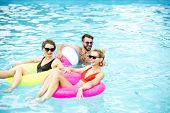 Group Of A Happy Friends Having Fun, Swimming With Inflatable Toys In The Swimming Pool Outdoors Dur poster