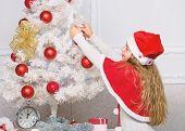 Girl Kid Decorating Christmas Tree. Cherished Holiday Activity. Kid In Santa Hat Decorating Christma poster