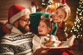 Christmas Eve. Family Father, Mother  And Child Reading Magic Book At Home Near The Fireplace And Th poster