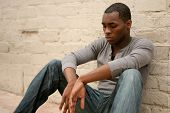 Depressed  African American Man Leaning Against Alley Wall