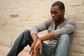 Homem Africano-americano deprimido, encostado à parede do beco