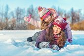 Little girl and her mother playing outdoors at sunny winter day. Active winter holydays concept. poster