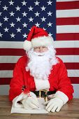Santa Claus writes a letter. Santa sits at his desk at the North Pole and prepares to write his list poster