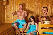 stock photo of sauna  - A young woman and two men with towels sitting in a sauna and posing with the thumbs up sign - JPG