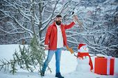 Funny Santa Man Posing With Axe And Christmas Tree. Hipster Woodsman With Christmas Tree. A Handsome poster