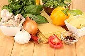 Vegetarian lasagna ingredients on wooden background