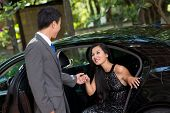 foto of polite  - Elegant man helping his wealthy lady to come out of the car - JPG