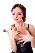 beautiful girl with chocolate candies on her fingers