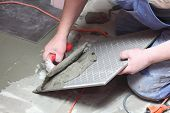 Construction Worker Is Tiling At Home Tile Floor Adhesive