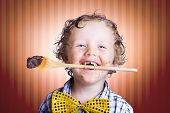 picture of chocolate spoon  - Adorable Little Boy With Wooden Cooking Spoon In Mouth And Choc Smeared Face Baking Chocolate Easter Cake - JPG