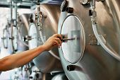 stock photo of cistern  - Male hand closes hatch of brewery tank - JPG