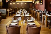 Roomy hall in restaurant with wooden furniture and walls of red bricks