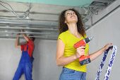 Woman with an electric screwdriver and man is working with a ceiling profile in under construction a