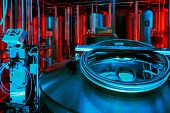 Brewing equipment at hall of microbrewery in red and blue lighting